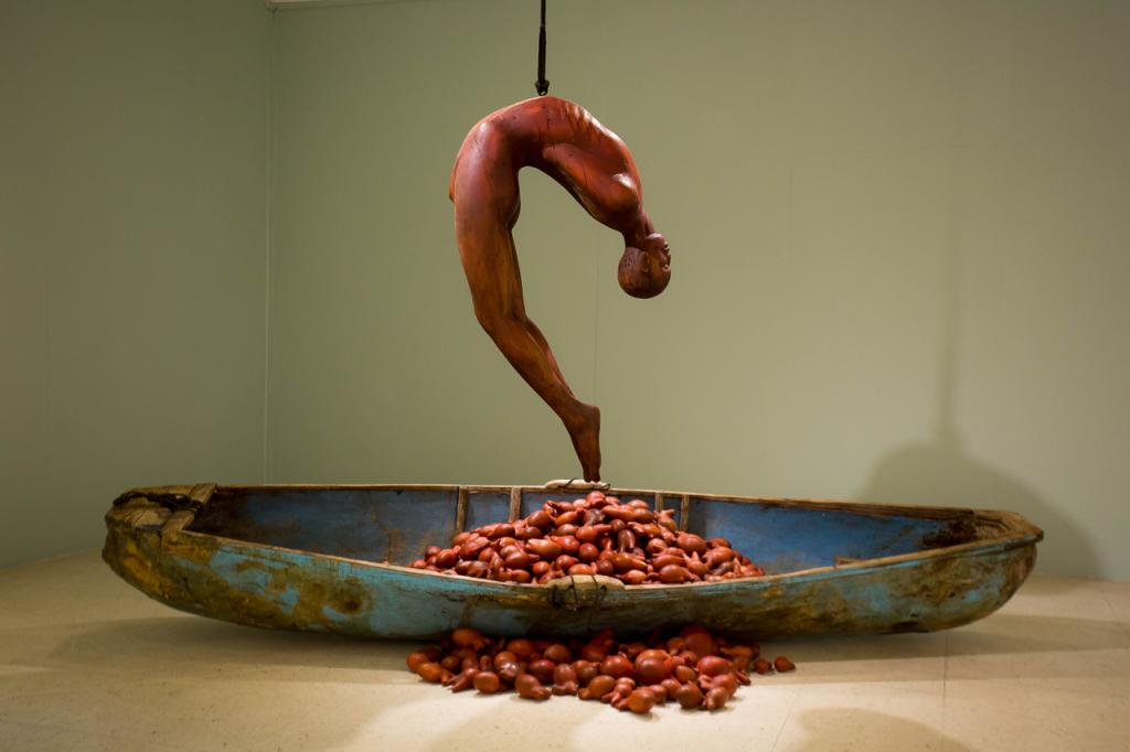 """HEART OF A MAN, 2019, wood and fiberglass canoe, cedar and mahogany hearts, rope, metal 18 x 18ft. """"As men journeyed across the Atlantic, shackled on ships, stripped of everything and unable to protect their loved ones - their hearts were ripped from their chests."""""""