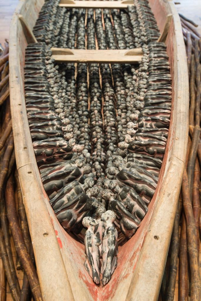 THEIR SPIRITS GONE BEFORE THEM detail, cottonwood canoe, 1,357 resin miniatures of the Redemption Song monument, dried sugar cane, 72 x 240 x 33 inches.